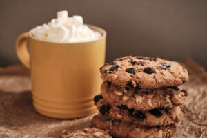 Stack of peanut and chocolate chip cookies with a hot chocolate drink in the background