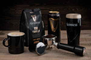 Guinness beer and coffee on wooden table with a dark wood background