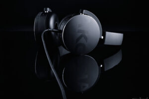 Pair of AKG headphones on gloss black table with black background