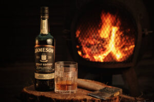 Bottle of Jamesons Stout Edition whiskey with open fire in the background