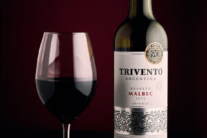 Bottle of red Trivento wine and glass with red background